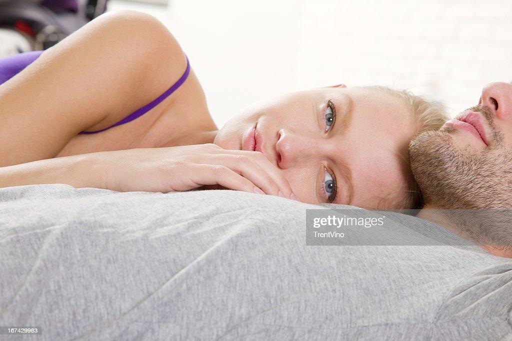 Pareja de yacer en la cama : Foto de stock