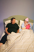 Couple lying in bed, woman bundled up with hot water bottle