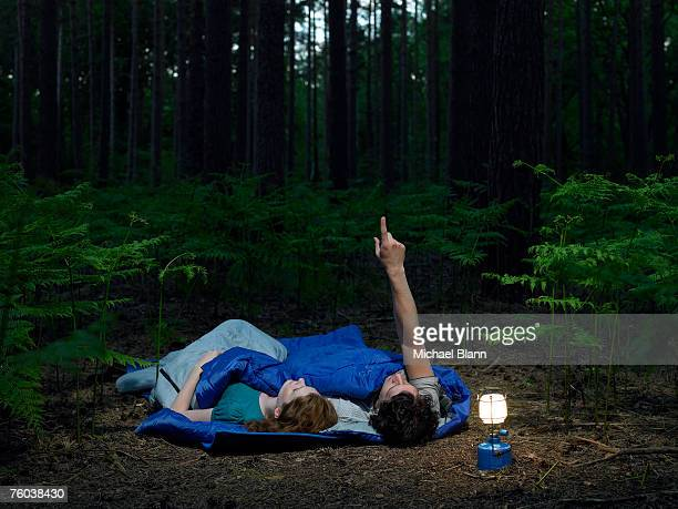 Couple lying in sleeping bags in forest with illuminated lantern, man pointing upwards