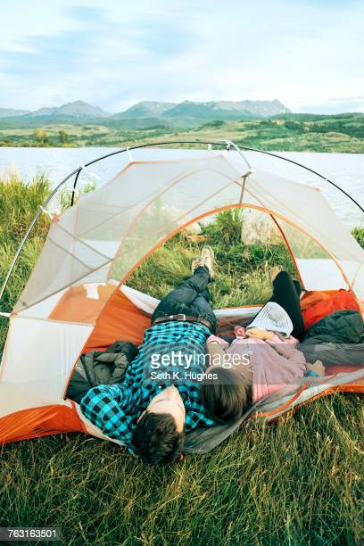 Couple lying in tent, heads outside of tent, rear view, Heeney, Colorado, United States