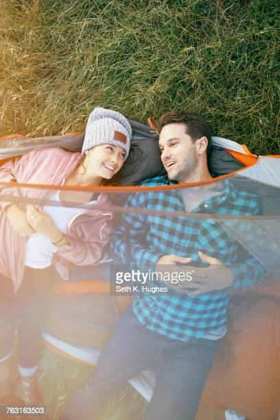 Couple lying in tent, heads outside of tent, smiling, overhead view