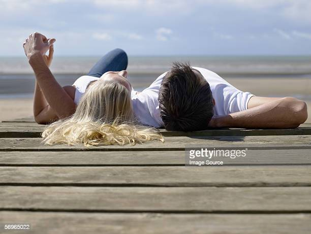 Couple lying on a deck on the beach