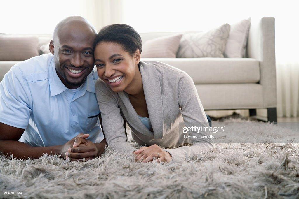 Couple lying on a rug : Stockfoto