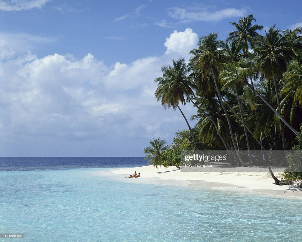 Couple lying on a sandy beach with palm trees, Maldives : Stock Photo