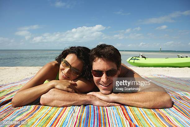 Couple lying on beach blanket, smiling, portrait, close-up