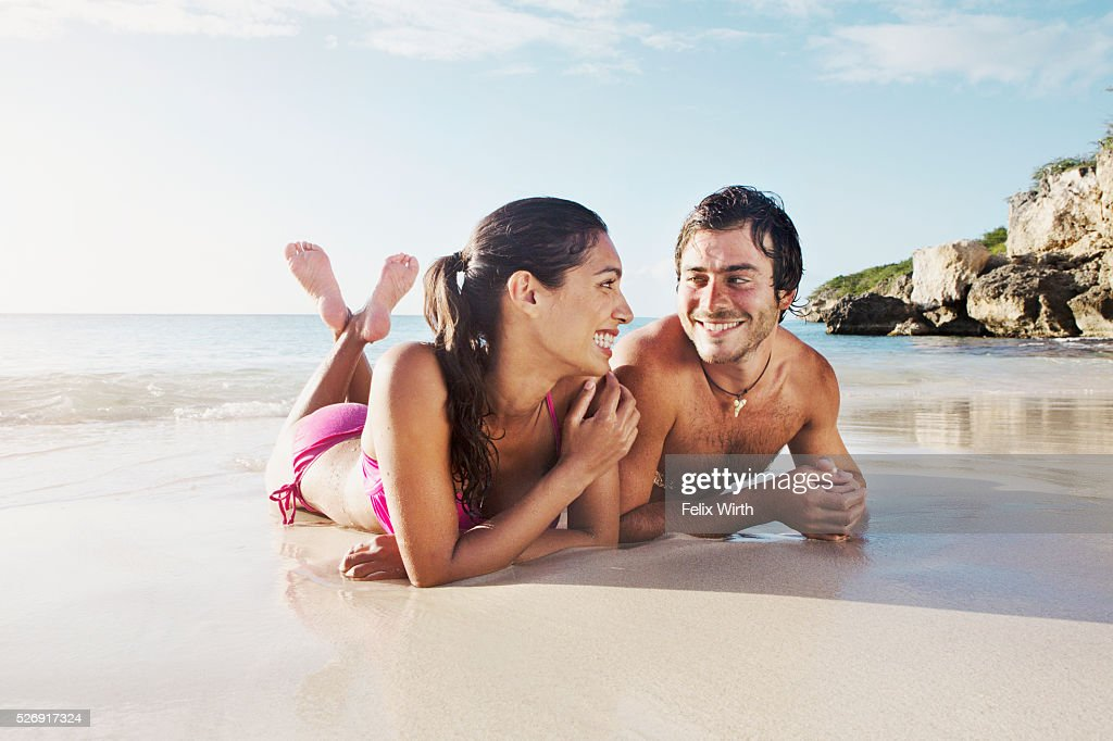 Couple lying on beach : Bildbanksbilder