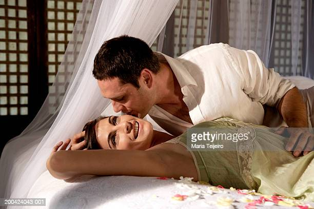 Couple lying on bed, man kissing young woman's cheek, close-up