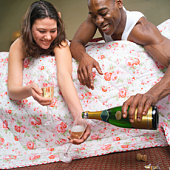 Couple lying on bed, man pouring champagne into glasses held by woman