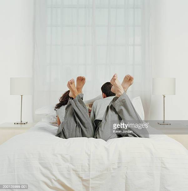 Couple lying on bed, reading newspaper, rear view