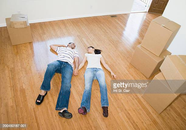 Couple lying on floor beside stacks of cardboard boxes, elevated view
