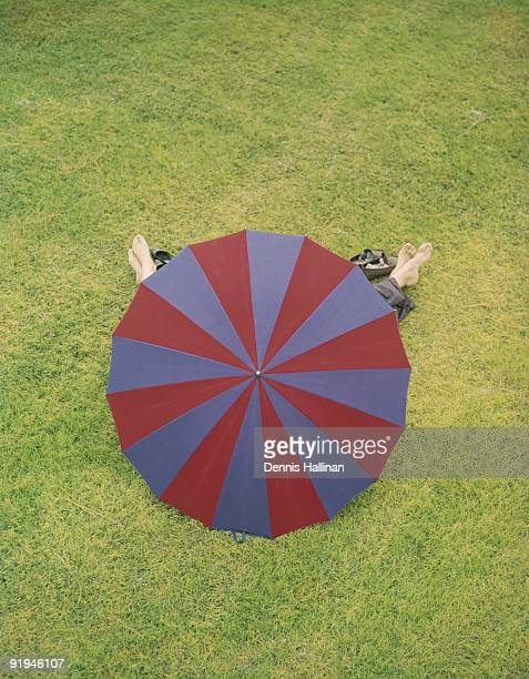 Couple lying on grass behind beach umbrella barefoot