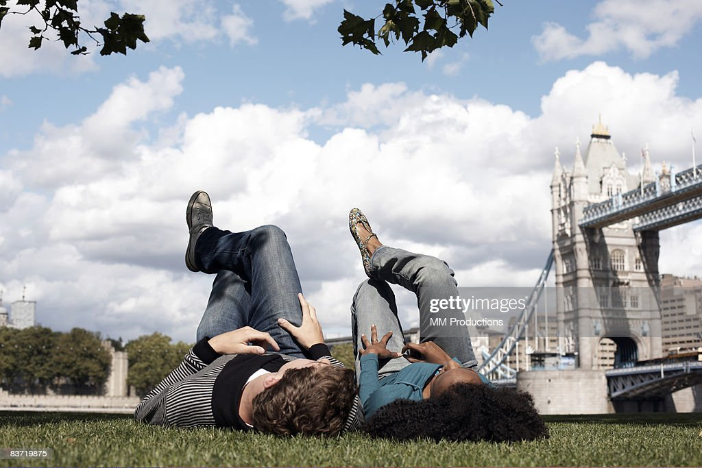 Couple lying on grass overlooking Tower Bridge : ストックフォト