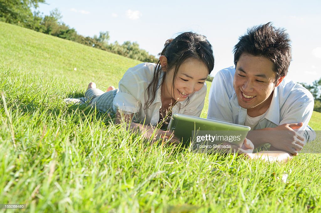 Couple lying on grass : Stock Photo