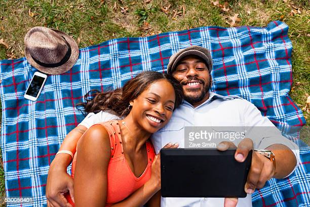 Couple lying on grass watching movie on tablet