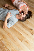 Couple lying on hard Wood Floor