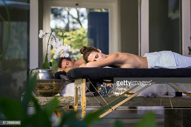 Couple lying on massage tables in resort