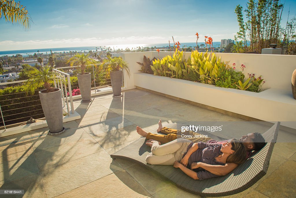 Couple lying on sun lounger in penthouse rooftop garden, La Jolla, California, USA