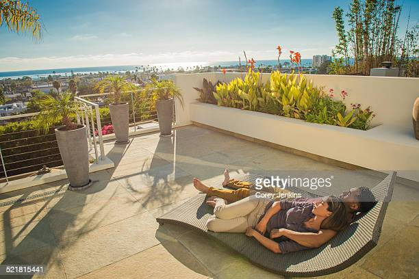 Couple lying on sun lounger in penthouse rooftop garden, La Jolla, California, USA