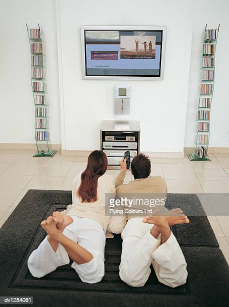Couple Lying on the Floor of Their Sitting Room Home Shopping on the Plasma Screen