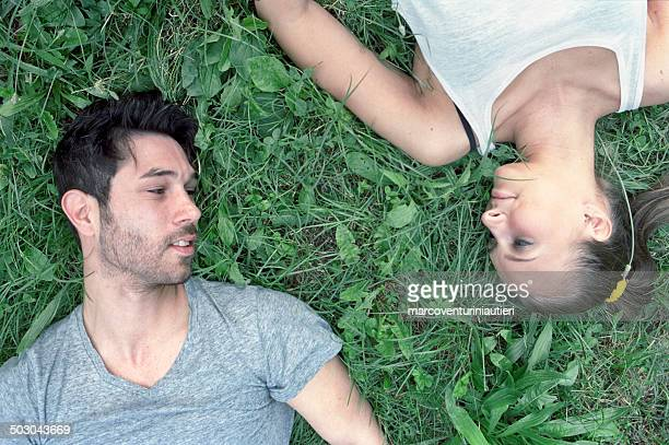 Couple, lying on the grass, looking at each other