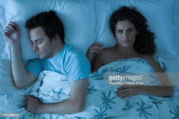 Couple lying together in bed, woman awake looking away contemplatively