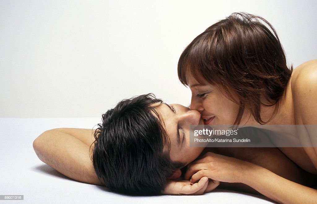 Couple lying together, kissing : Stock Photo