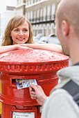 Couple mailing letter in mailbox, London, England
