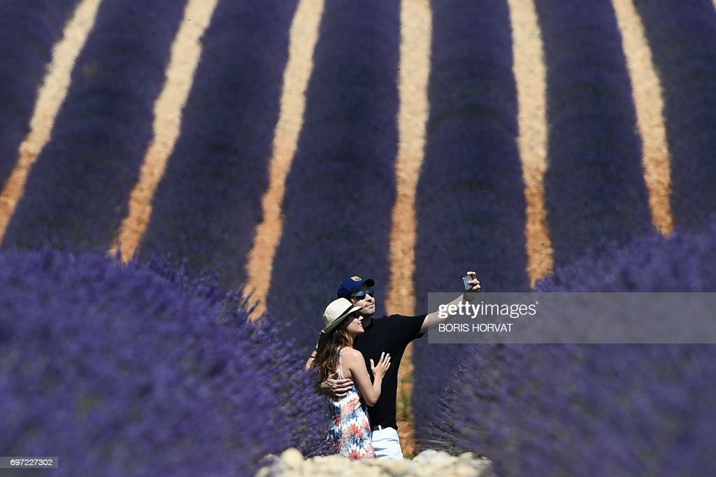 TOPSHOT - A couple makes a selfie in a lavender field in Valensole, southern France, on June 18, 2017. /