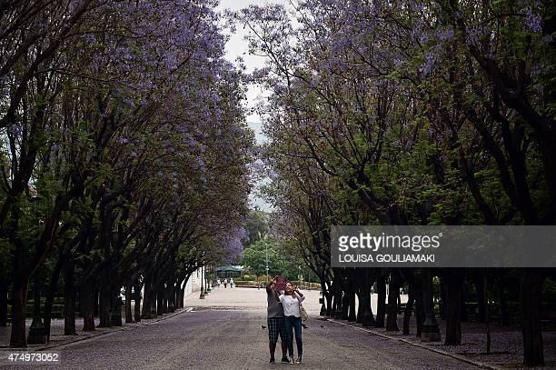 A couple makes a selfie photo after a downpour at a central Athens alley on May 28 2015 AFP PHOTO / LOUISA GOULIAMAKI