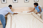 Couple making a bed together