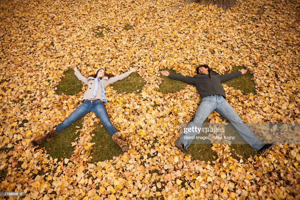 Couple making angel in autumn leaves