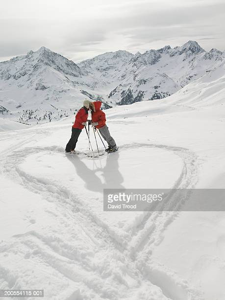 Couple making heart symbol on snow covered mountain, side view