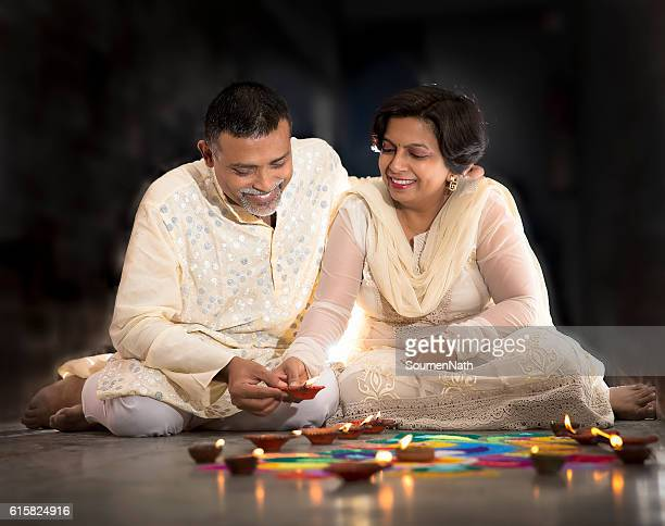Couple making Rangoli, decorating with Oil lamps for Diwali