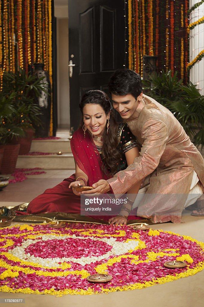 Couple making rangoli on Diwali