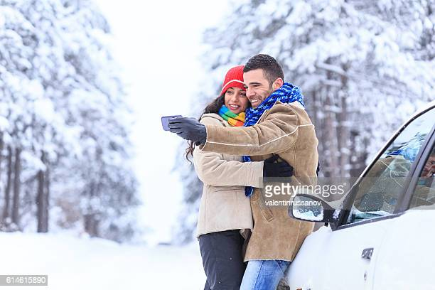 Couple making selfie in front of a car in forest
