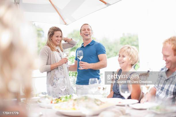 Couple making toast at table