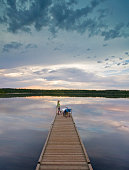 A couple, man and woman sitting at the end of a long wooden dock reaching out into a calm lake, at sunset.