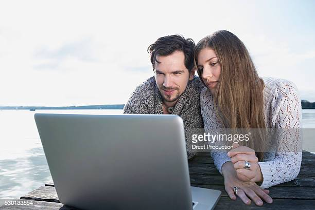Couple man woman wooden jetty laptop computer