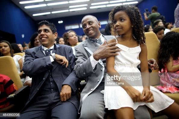 Couple Marcel and Geraldo sit with their daughter Kevellen before marrying at what was billed as the world's largest communal gay wedding on December...