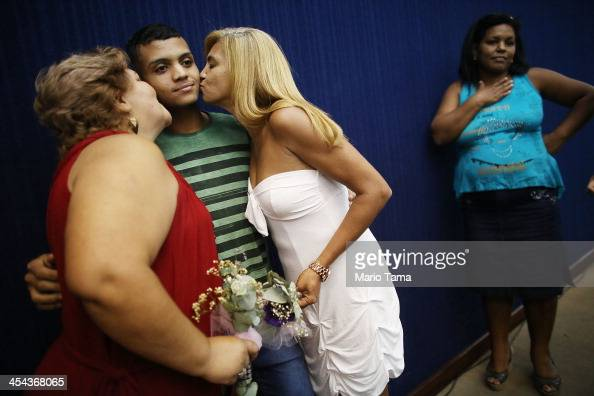 Couple Marcia and Jaqueline kiss Marcia's son Gustavo while posing before marrying at what was billed as the world's largest communal gay wedding on...