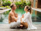 Caucasian ethnicity couple meditate together by the pool