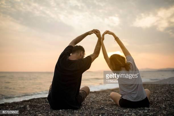 Couple Meditating At Beach