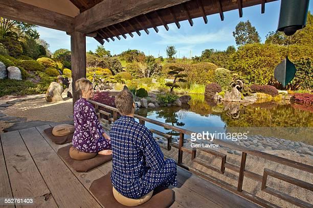 Couple meditating in a zen garden