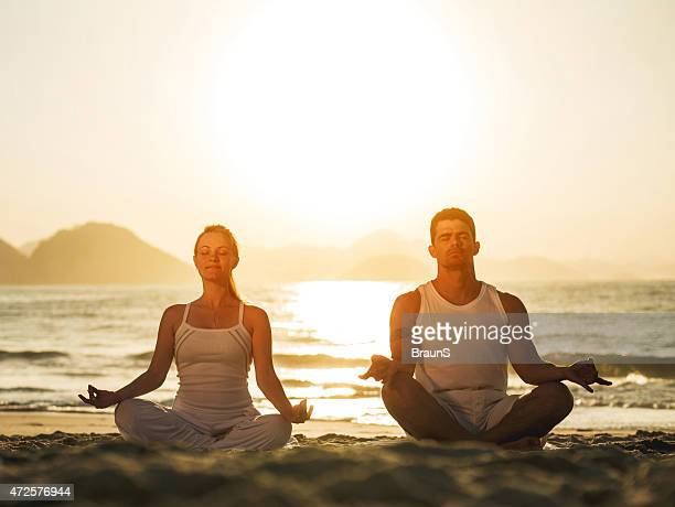 Couple meditating on the beach at sunset. Copy space.