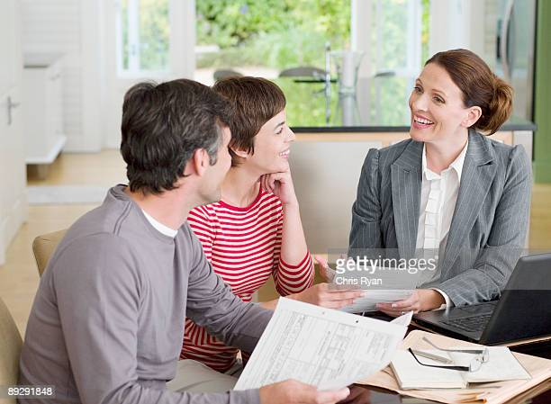 Couple meeting with financial advisor in dining room