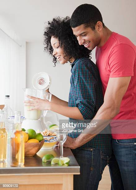 Couple mixing margaritas in kitchen