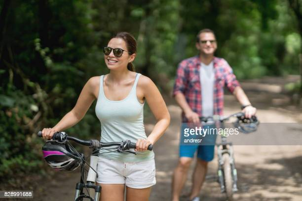 Couple mountain biking and looking very happy outdoors