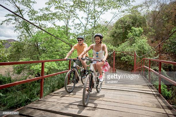 Couple mountain biking crossing a bridge