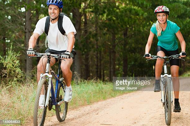 Couple mountain biking on dirt road