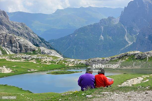 Couple mountain walkers reading map at lake in the Dolomites Italy